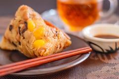 Close-upzongzi of kleverige rijstbol met thee stock foto