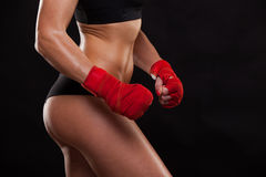 Close view of athletic girl posing in red bandages,  on the dark background boxing fighter kickbox Royalty Free Stock Photos