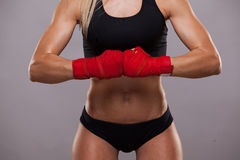 Close view of athletic girl posing in red bandages, isolated on the grey background boxing fighter kickbox Royalty Free Stock Image