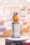 Close view of a blender with an orange and cinnamon sticks on a Stock Images