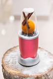 Close view of a blender with an orange and cinnamon sticks on a Royalty Free Stock Photos