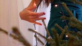 Slow motion blond girl hangs garland on Christmas tree. Close view blond girl with loose flowing hair in azure dress hangs garland on Christmas tree at home slow stock video