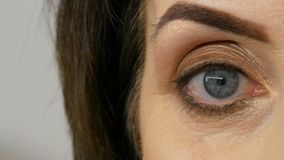 Close view of blue eye of middle-aged adult woman with beautiful make-up in a beauty salon. stock video footage