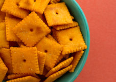 Close view of a bowl of cheese crackers. Top close view of a bowl of cheese crackers atop an orange background illuminated with natural light Royalty Free Stock Image