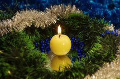 A close view of a candle. A close view of a candle and some big sparkly christmas tree decorations royalty free stock image