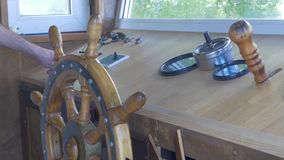 Close view into captain`s cabins, navigation equipment and captain`s hand on rudder during cruising. Captain`s cabin of Stock Images