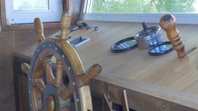 Close view into captain`s cabins, navigation equipment and captain`s hand on rudder during cruising. Captain`s cabin of Stock Photo