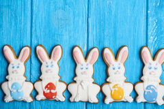 Close view at colorful easter rabbit cookies on blue wooden background Stock Image