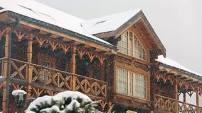 Close view of cottage with mezzanine in mountain village during heavy snowfall with russian style carved wooden facade. Snow falling on log chalets at ski stock video
