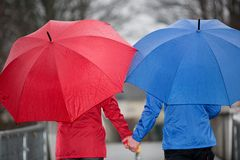Close view from a couple hand in hand walking in the rain Stock Photography