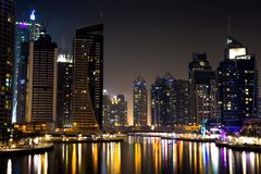 Dubai Marina Buildings At Night. A close view of the Dubai Marina at night, with the lights from the buildings reflecting off the water royalty free stock images