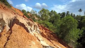 Close View Fairy Stream Red Rocks against Jungles. Close view Fairy stream old strange limestone rock formations against tropical jungles and blue sky with stock video