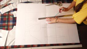 Close view of fashion designer woman hands working in studio. Caucasian female tailor drawing the layout for clothes on. Fashion designer woman working in studio stock video