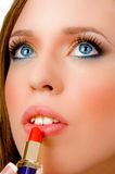 Close view of female applying lipstick Stock Image