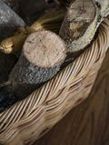 Close View of Firewood and Fireplace Broom in a Basket on a Hardwood Floor stock photography