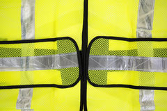 Close view of fluorescent yellow safety vest. A very close view of a florescent yellow safety vest with silver reflective stripes Stock Images