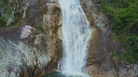 Close View Foamy Waterfall Falls into Lake among Rocky Banks stock video footage
