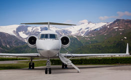 Close view of the front of a private jet. With mountains in the background stock image