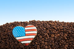 Close view at gingerbread heart shaped and coffee beans. Close view at gingerbread heart shaped cookies with american flag. Scattered coffee beans on blue Stock Image