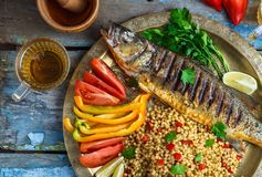 Close view of grilled sea bass with vegetables and ptitim, middle eastern cuisine.  stock images
