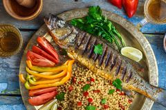Close view of grilled sea bass with vegetables and ptitim, middle eastern cuisine.  royalty free stock photo