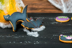 Close view at homemade halloween sweets. Gingerbread cookies  cat. and bat over black wooden table with pumpkin on a back and spiderweb. Shallow depth of field Stock Image