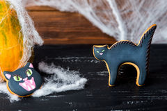 Close view at homemade halloween sweets. Gingerbread cookies  cat head and cat over black wooden table with pumpkin on a back and spiderweb Stock Photography