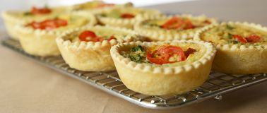 Close View of Individual Mini Quiche. A close up view individual mini quiche topped with slices of tomato and parsley sitting on a wire rack stock photography