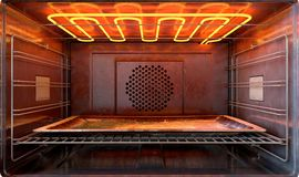 Inside The oven. A close view inside a  hot operational household oven with an empty tanished baking tray - 3D render Royalty Free Stock Images
