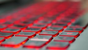 Focus on a gaming laptop keyboard. The focus changes. Close view of the keyboard of a laptop computer. The keyboard has keys with red lights. Focus on some keys stock footage