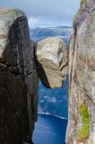 Close view of a Kjeragbolten rock with a blue fjord Lysefjorden in the background way under stock photos