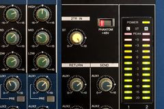 Close view of knobs and lighted vu mete. R peaking on a blue audio mixing table stock images