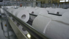 Close View of Long Toilet Paper Conveyor. Close view of long conveyor with toilet paper moving slowly in large light factory workshop stock footage