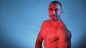 Close view of male athlete flexing muscles, showing big arms and shoulders. Male Fitness Model Flexing muscles, isolated on blue background. Studio shot stock footage