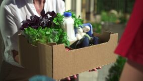 Close view of man courier giving to woman box of fresh food while standing at door of house spbd.