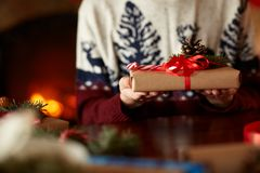 Close view of man`s hands holding and showing handmade wrapped Christmas gift near fireplace. Male in knitted sweater stock image