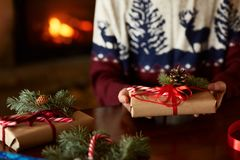 Close view of man`s hands holding and showing handmade wrapped Christmas gift near fireplace. Male in knitted sweater stock photo