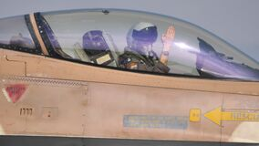 Close view of a military pilot in the cockpit of a fighter jet greeting