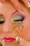 Close view of model curling her eyelashes Stock Photo