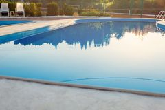 Close view of modern swimming pool at sunset at hotel. Sunlight at surface. Summer vacation, holidays, relax, summer activities. Concept royalty free stock photography