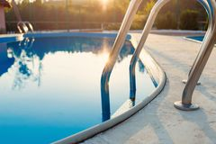 Close view of modern swimming pool at sunset at hotel. Sunlight at surface. Summer vacation, holidays, relax, summer activities. Concept royalty free stock images