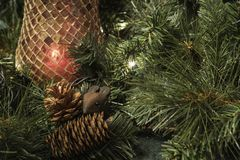 Close view of mouse and pine cones Christmas display. With red glass mosaic candleholder and greenery. Horizontal view Royalty Free Stock Image