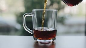 A close view of pouring black tea from a glass teapot into an empty glass cup. A close-up of a hand pouring tea from a clear glass teapot into a transparent stock footage