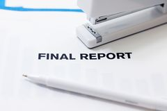 Final Report On Desk. Close view of the print Final Report on paper with a white stapler above and white pen below royalty free stock images