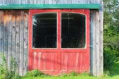 Close view of red barn doors on a weathered wood building with large windows and green door track stock image