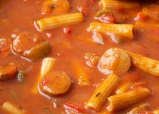 Close view of rigatoni pasta with sausage. Close view of rigatoni pasta with slices of sausage in a tomato sauce illuminated with natural lighting stock image
