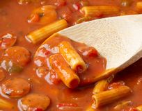 Close view of rigatoni pasta and sausage with a wood spoon. Close view of rigatoni pasta and slices of sausage in a tomato sauce with a wood spoon illuminated royalty free stock photo