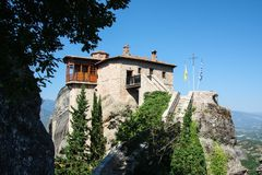 Close view of small rock monastery Rousanou St. Barbarain and mauntains. Meteora, Greece royalty free stock image