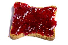 Toasted bread with jam. Close view of a toasted bread with berry jam spread  isolated on a white background Stock Photos