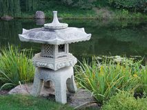 Japanese stone lantern. A close view of a traditional Japanese stone lantern in a water garden Stock Images